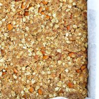 Unbaked apricot almond oat slice mixture in a parchment paper lined baking pan.