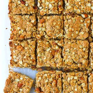Apricot almond square shaped oat slices on parchment paper. Oat slice on bottom left corner is sticking out.