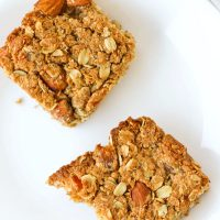 Two apricot and almond oat slices on a white round plate.