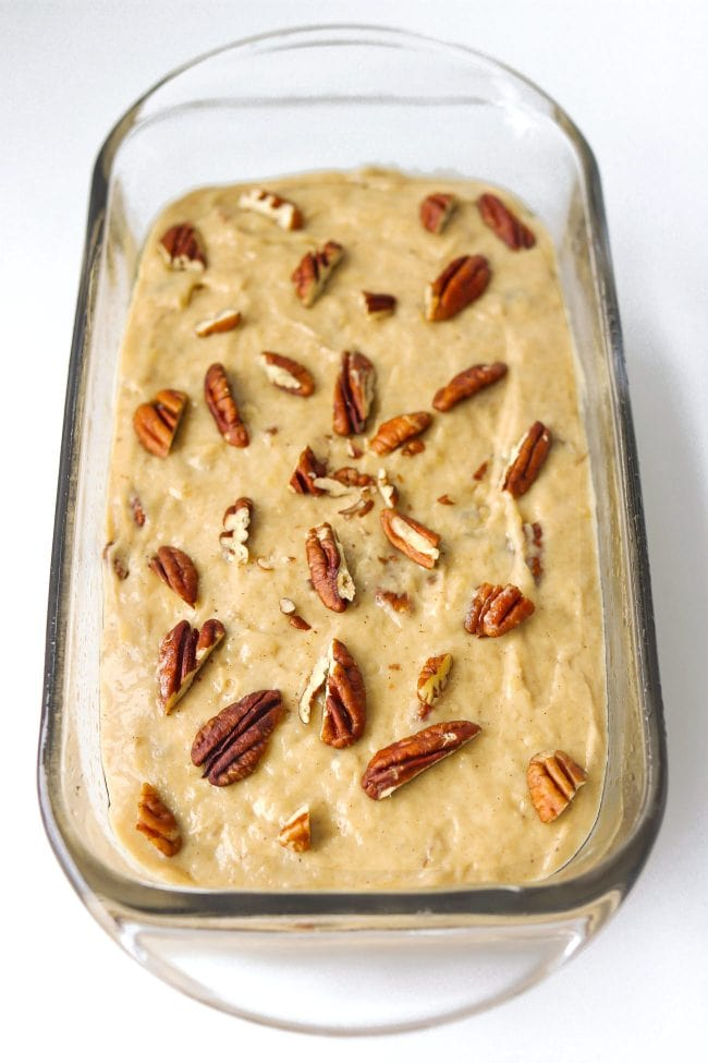 Batter topped with chopped pecans in a glass loaf dish.