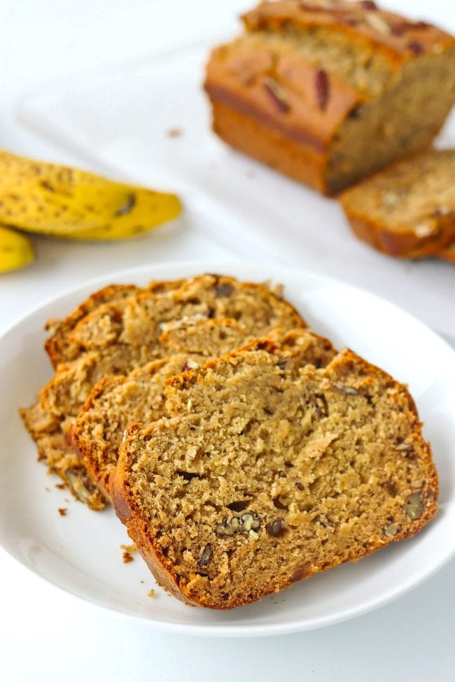 Four slices of Banana Pecan Bread on a white plate. Loaf on parchment paper lined cutting board and ripe bananas in the back.