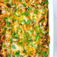 Large baking dish with Spicy BBQ Chicken Penne Pasta with corn, broccoli, melted cheese, and garnished with chopped coriander and spring onion.
