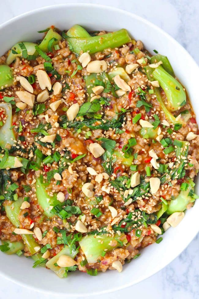 Ground pork and bok choy peanut sauce stir-fry in white round serving bowl topped with sesame seeds, chopped peanuts, coriander, and spring onion.