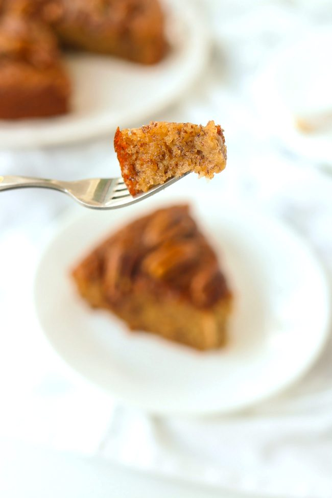 Fork holding up a bite of almond banana cake above a plate with a slice. Rest of the cake on a plate in the back.