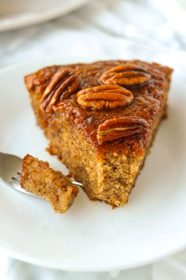 Close up of slice of almond meal banana cake topped with honey pecan glaze on a plate with a small bite of the cake on a fork.