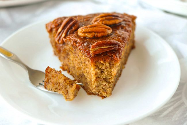 A slice of almond meal banana cake topped with honey pecan glaze on a plate with a small bite of the cake on a fork.
