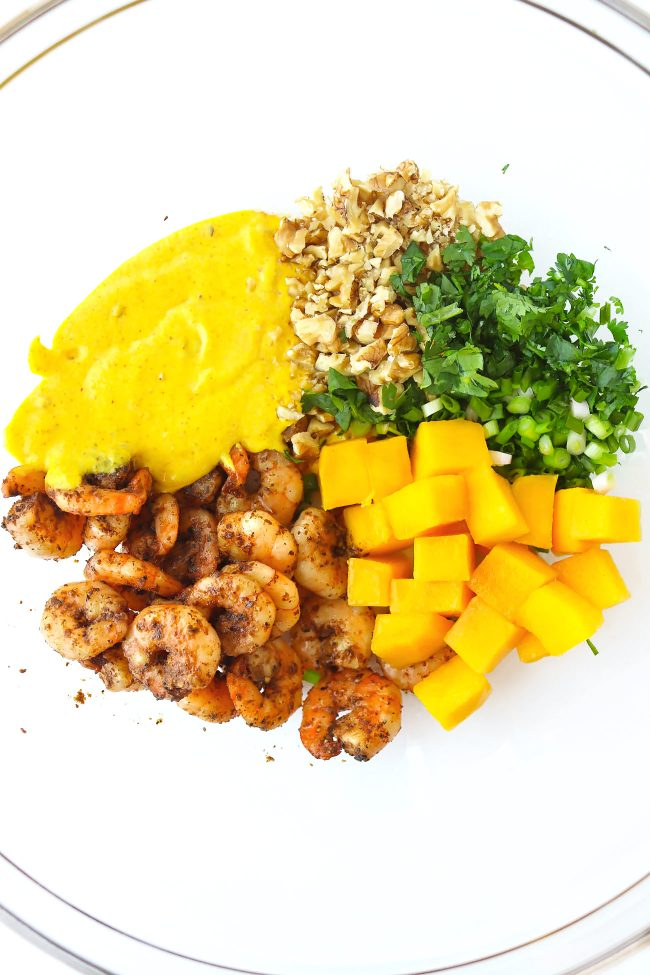 Pan-seared cajun shrimp, cubed mango, creamy spicy mango mayonnaise, chopped coriander, spring onion, and walnuts in a large mixing bowl.