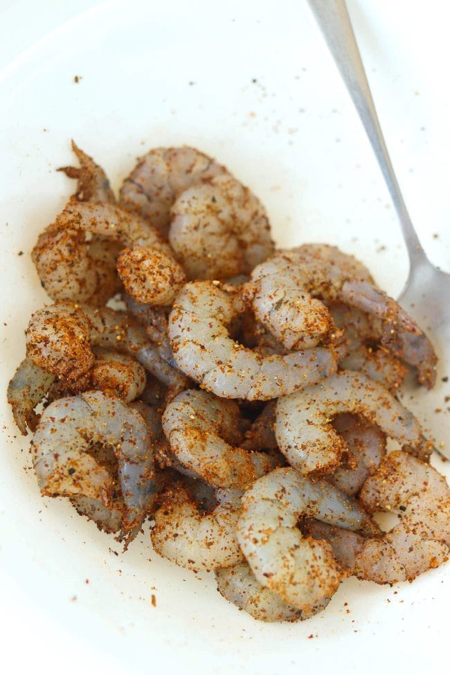 Shrimp coated with seasonings in a bowl with a spoon.