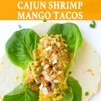 Two open-faced Cajun Shrimp Mango Tacos with butter lettuce and topped with toasted coconut flakes on a white background. Spring onion and toasted coconut flakes scattered around the tacos.