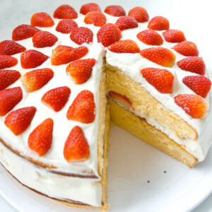 Top front angle view of strawberry lemon cream layer cake on a platter with a slice cut out to show inside of cake.