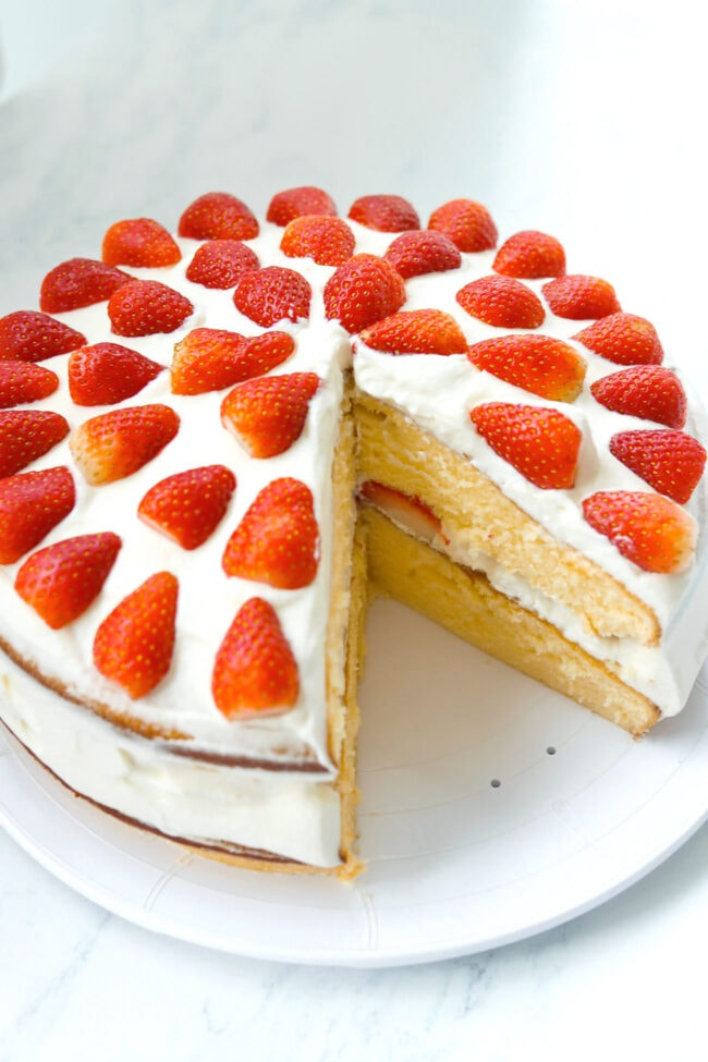 Top front angle view of strawberry cream layer cake on a platter with a slice cut out to show inside of cake.