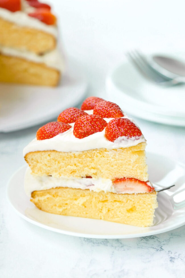 Left side view of slice of strawberry cream layer cake on plate with fork. Rest of the cake on a platter and stacked plates with a fork behind.
