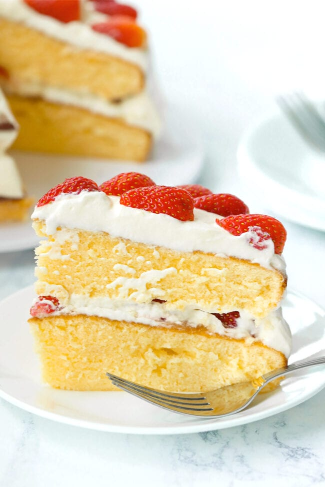 Side view of strawberry cream cake on a plate with a fork. Stack of plates and a fork and rest of the cake on a platter behind.