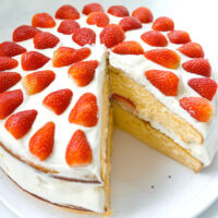"Overhead front view of layer cake on a platter with a slice cut out to show inside of cake. Text overlay ""Strawberry Lemon Cream Cake""."