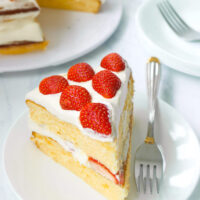 "Front view of a slice of cake on a plate with a fork. Text overlay ""Strawberry Lemon Cream Cake""."