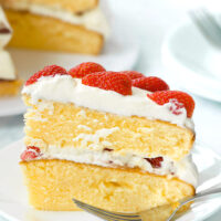 "Side view of slice of strawberry lemon cream layer cake on a plate with a fork. Text overlay ""Strawberry Lemon Cream Cake""."