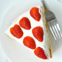 "Overhead view of a slice of Strawberry lemon Cream Cake on a plate with a fork. Text overlay ""Strawberry Lemon Cream Cake""."