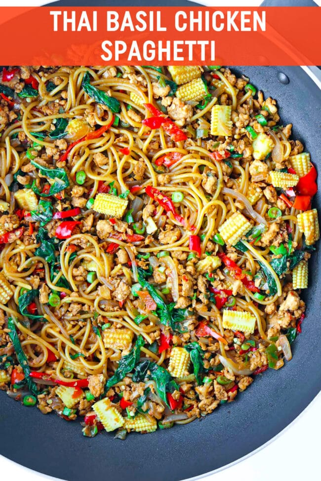 "Overhead view of large wok with spaghetti tossed with baby corn, green beans, holy basil, ground chicken, chilies, onion, and garlic in a brown sauce. Text overlay ""Thai Basil Chicken Spaghetti""."