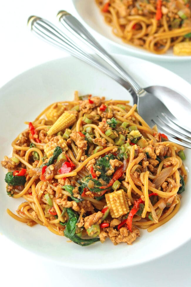 Two diagonally placed white round plates with spaghetti tossed with ground chicken, garlic, red and green chilies, onion, baby corn, green beans, and holy basil in a brown sauce. Fork and spoon on the top corner of the front plate.