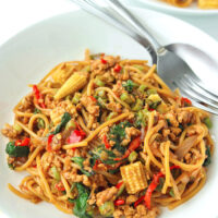 "Two diagonally placed white round plates with spaghetti tossed with ground chicken, garlic, red and green chilies, onion, baby corn, green beans, and holy basil in a brown sauce. Fork and spoon on the top corner of the front plate. Text overlay ""Thai Basil Chicken Spaghetti""."