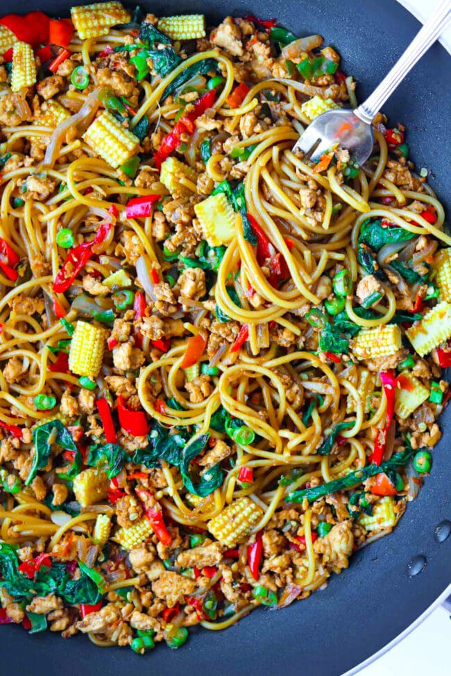 Top view of a large wok with spaghetti tossed with ground chicken, chilies, onion, baby corn, green beans in a brown stir-fry sauce. A fork is twirled around spaghetti in the top right corner.