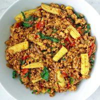 Top view of ground chicken Thai basil stir-fry with sliced baby corn in a large white serving bowl.