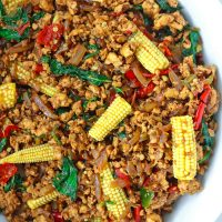 Ground chicken Thai basil stir-fry with sliced baby corn in a large white serving bowl.
