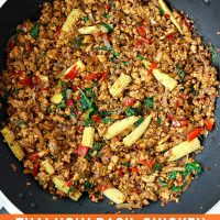 Thai holy basil chicken stir-fry with baby corn in a large wok.