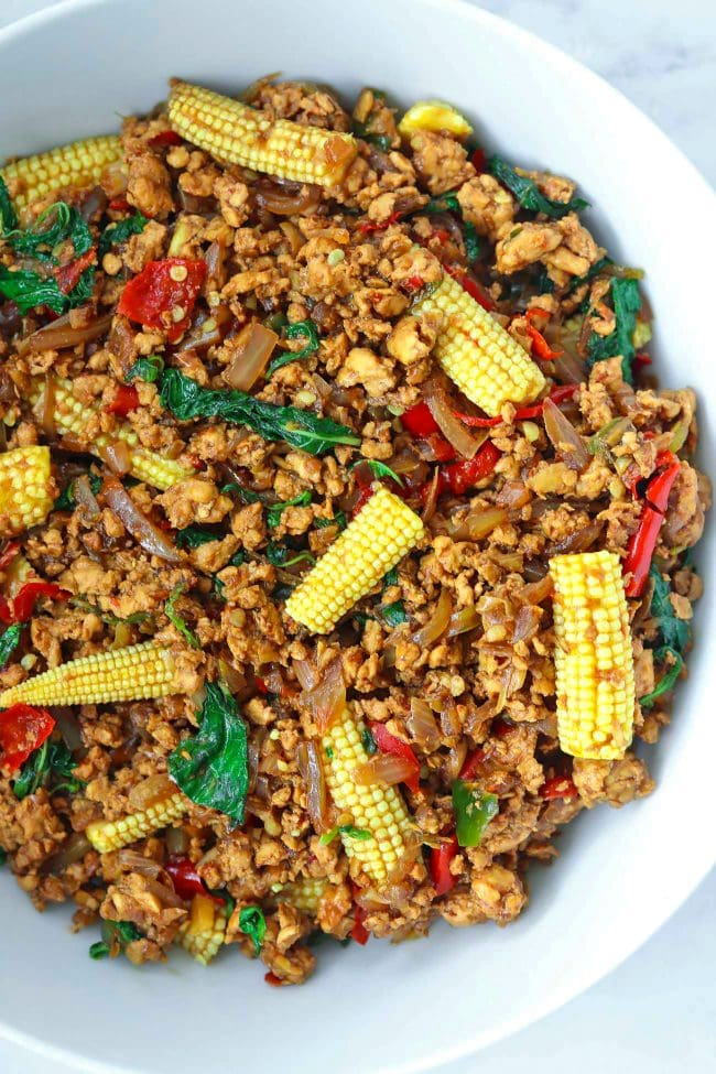 Close up of ground chicken Thai basil stir-fry with sliced baby corn in a large white serving bowl.