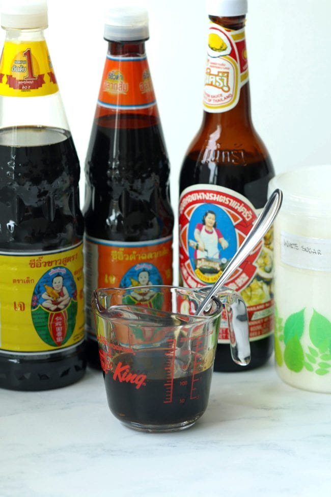 Measuring cup with sauce and a spoon. Light and dark soy sauce bottles, oyster sauce bottle, and white sugar in a sealed airtight container behind.