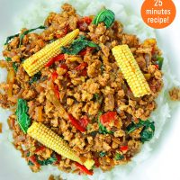 Top view of plate with rice topped with ground chicken Thai basil stir-fry with sliced baby corn.