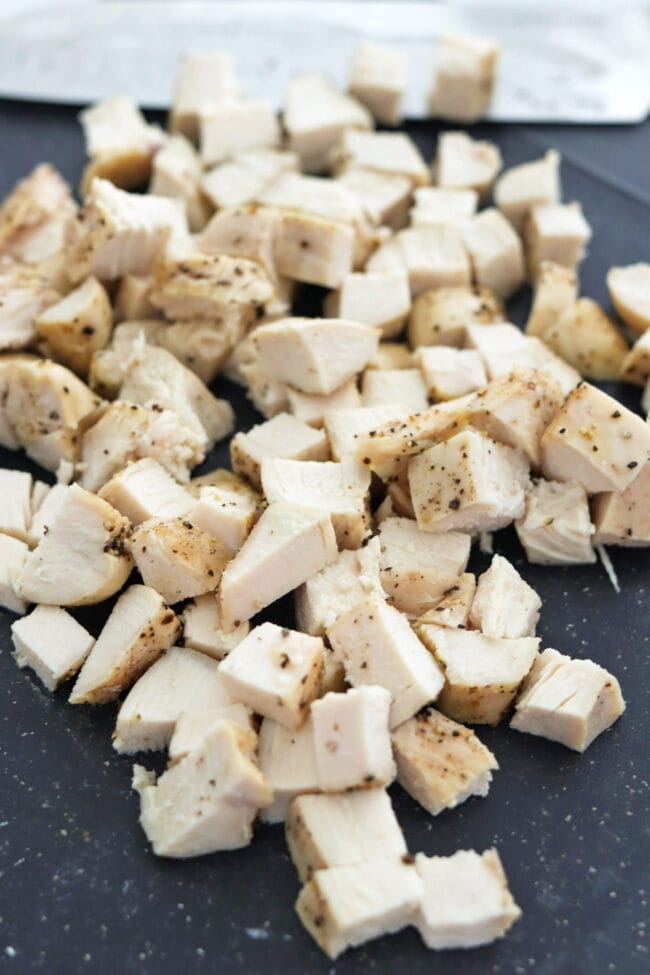 Diced chicken on a cutting board with a knife.