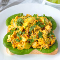 Front view of coronation chicken salad piled on a slice of bread with lettuce on a plate. Knife and fork and green grapes in a bowl in the back.
