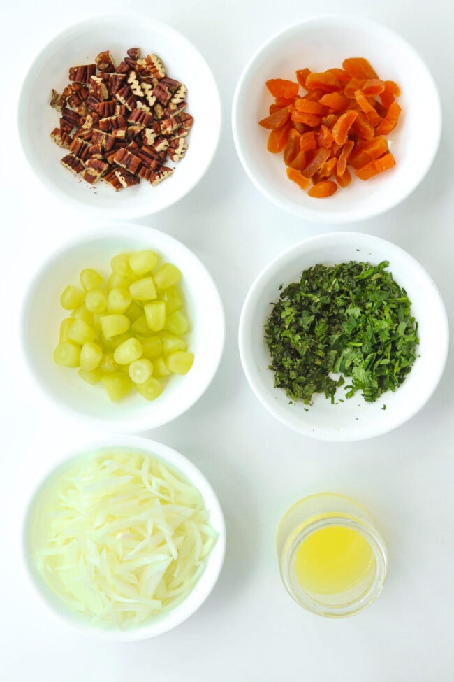 Small bowls with toasted chopped pecans, chopped apricots, sliced onion, halved green grapes, chopped mint leaves and coriander, sliced onion. Lemon juice in a small bottle.