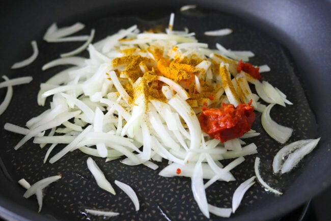 Sliced onion topped with curry powder, turmeric, and tomato paste in a pan with oil.
