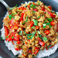"""Front view of ground pork stir-fry garnished with mint leaves and coriander on rice in a bowl with a spoon. Text overlay """"Lemongrass Pork Stir-fry""""."""