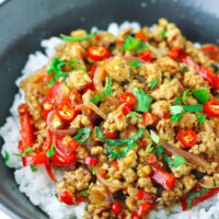 """Front view of ground pork stir-fry garnished with mint leaves and coriander on rice in a bowl. Text overlay """"Lemongrass Pork Stir-fry""""."""