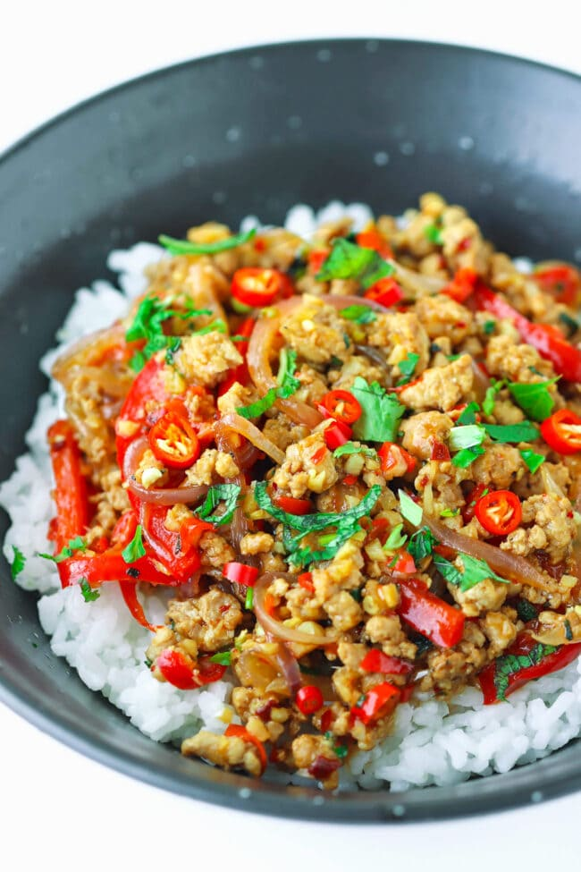 Ground pork stir-fry with onion, chilies, red bell pepper, mint, and coriander in a black bowl with rice.