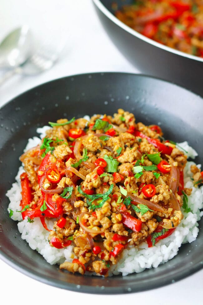 Lemongrass pork stir-fry in a bowl with rice and garnished with coriander and mint leaves. Wok with the stir-fry and utensils in the back.