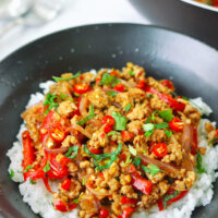 """Front view of ground pork stir-fry garnished with mint leaves and coriander on rice in a bowl. Wok with the stir-fry in the back. Text overlay """"Lemongrass Pork Stir-fry""""."""