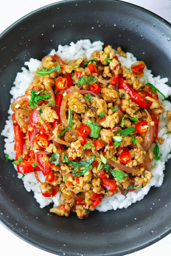 Overhead view of ground pork stir-fry garnished with coriander and mint leaves on rice in a bowl.