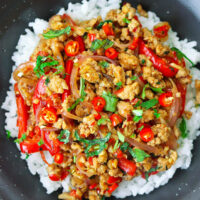 """Overhead view of Lemongrass Pork Stir-fry garnished with coriander in mint leaves on rice in a bowl. Text overlay """"Lemongrass Pork Stir-fry""""."""