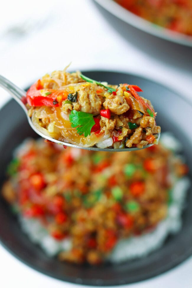Spoon holding up a bite of lemongrass ground pork stir-fry and rice above a bowl with the stir-fry and rice. Wok with the stir-fry behind.