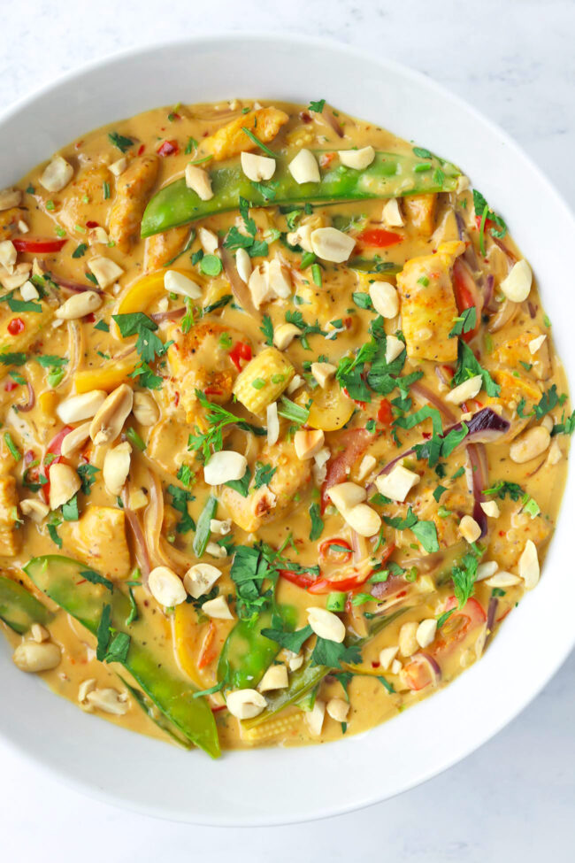 Top view of round serving bowl with creamy chicken curry with veggies garnished with chopped coriander and peanuts.