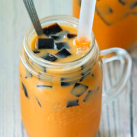 "Top front view of two diagonally placed mason mugs with Thai milk tea, grass jelly cubes, ice, boba straws, and tall spoons. Text overlay ""Thai Iced Milk Tea with Grass Jelly""."