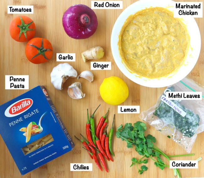 Labeled photo of ingredients for Butter Chicken Pasta Bake on wooden board.
