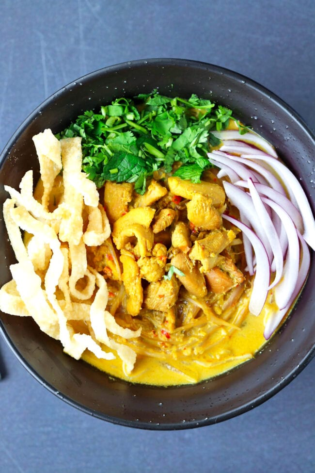 Top view of bowl with Khao Soi Gai with fried wonton wrapper strips, chopped coriander and mint leaves, and sliced red onion.