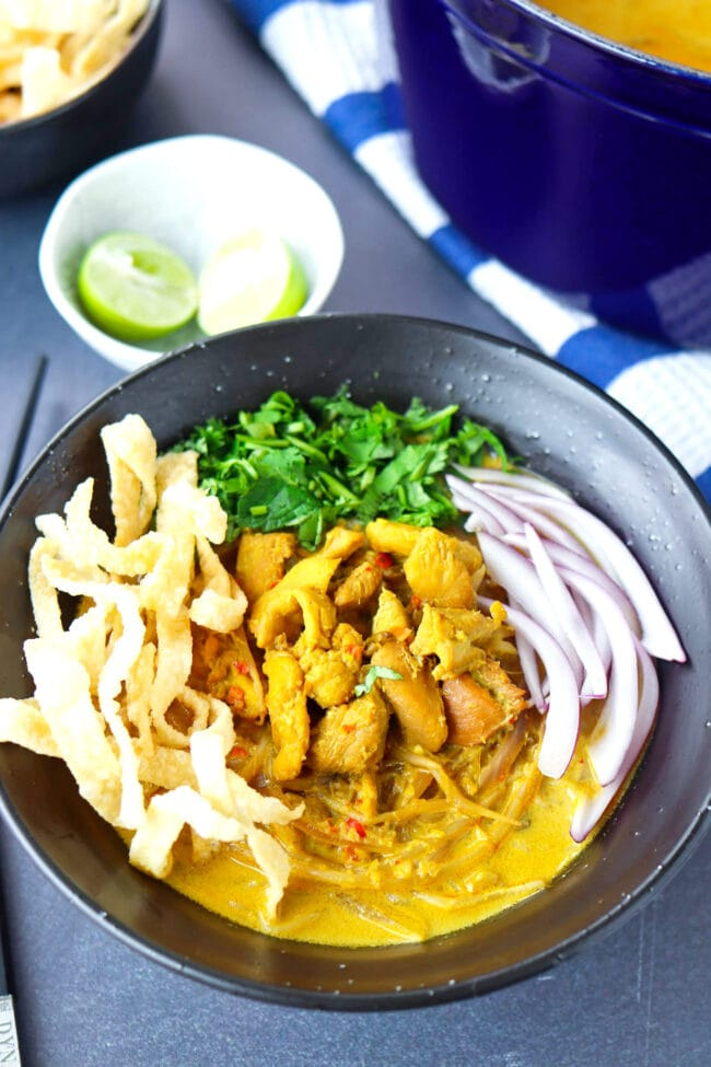 Front view of bowl with Khao Soi Gai topped with fried wonton wrapper strips, chopped coriander and mint leaves, and sliced red onion. Dutch oven with soup, and lime wedges and fried wonton wrapper strips in bowls behind.
