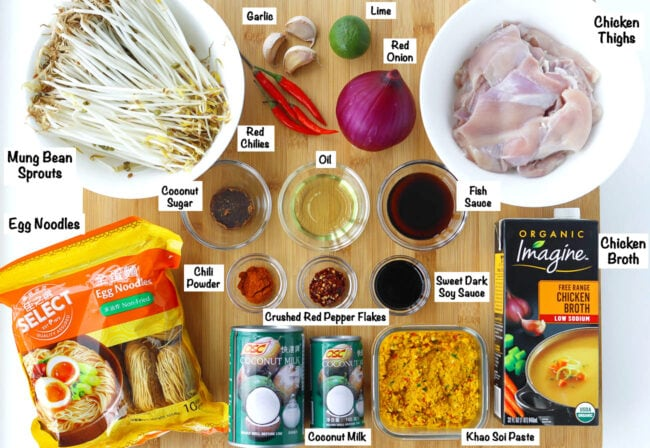 Labeled photo of ingredients for Khao Soi Gai on wooden board.