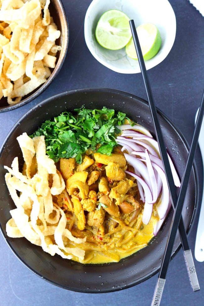 Top view of bowl with Khao Soi Gai with fried wonton wrapper strips, chopped coriander and mint leaves, and sliced red onion. Crossed chopsticks on top of side of the bowl, and lime wedges and crispy wonton wrapper strips in bowls behind.